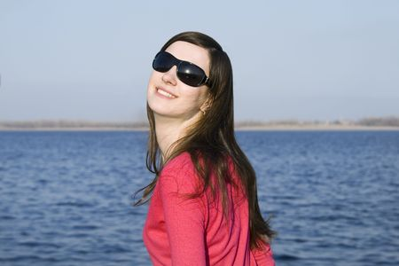 Closeup portrait of a beautiful young woman in sunglasses over big blue sky Stock Photo - 4721883