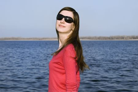 Closeup portrait of a beautiful young woman in sunglasses over big blue sky Stock Photo - 4721880