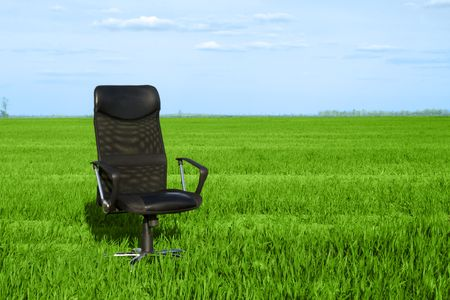 Office chair in a green grass with a deep blue sky