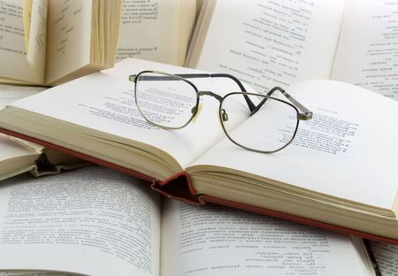 Many open books and glasses on it photo