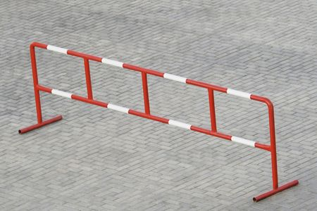 Metal barrier standing on the grey stone block paving Stock Photo - 4989622