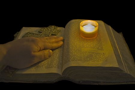 Male hand lies on ancient bible with a big christian cross Stock Photo - 4989617