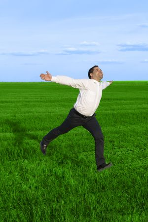 Running businessman in the meadow over clouds background photo