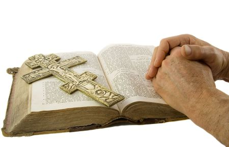 Hands closed in prayer and cross on an open bible isolated white photo