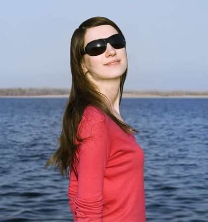 Closeup portrait of a beautiful young woman in sunglasses over big blue sky photo