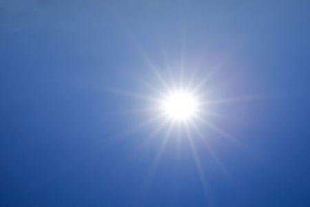 Hot sun over deep blue sky background photo