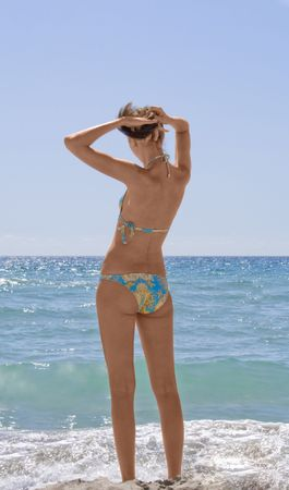 Beatifull brunette girl standing again sea photo