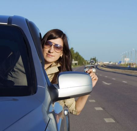 Happy young brunette driving silver car photo