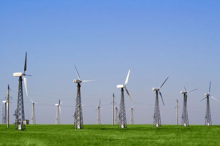 Wind farm turbines in green field over blue sky photo