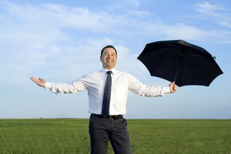 Happy businessman standing with umbrella in the meadow photo