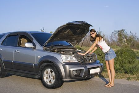 unexpectedness: beautiful brunette girl repairing the car
