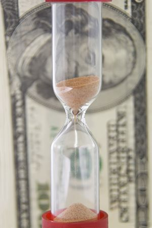 Closeup view of sand flowing through an hourglass on the background money photo