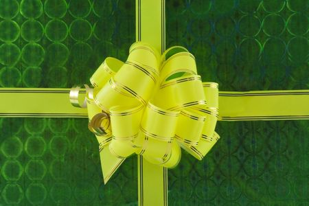 yellow holiday bow on green background Stock Photo - 5893573