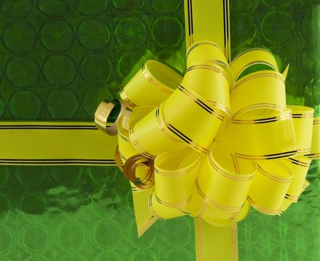 yellow holiday bow on green background Stock Photo - 6023627