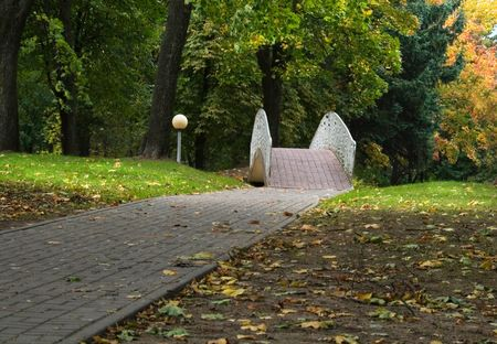 alley and  bridge in park at autumn day photo