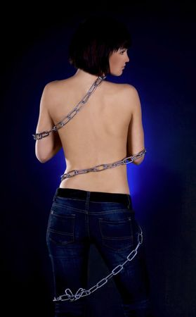 Sexy brunette with nude back in chains over black background Stock Photo - 6861192