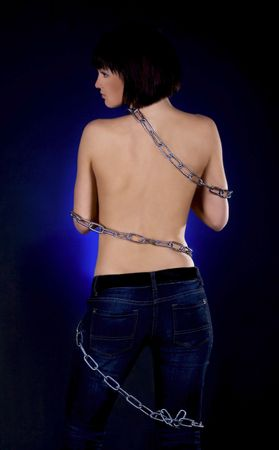 Sexy brunette with nude back in chains over black background Stock Photo - 7017499