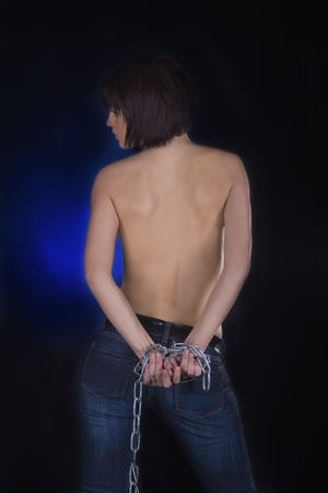 Sexy brunette with nude back in chains over black background Stock Photo - 7017508