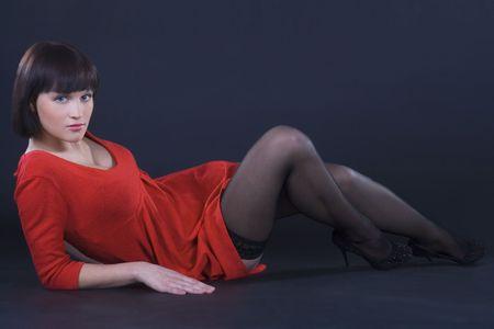 Beautiful brunette girl posing in studio on dark background photo