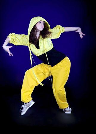 Teenage girl dancing hip-hop in the darkness photo