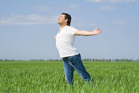 young man moves in a green field of grass to meet the sun photo