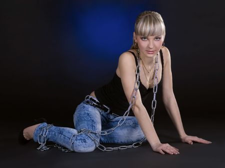 Sexy blonde in chains over black background photo