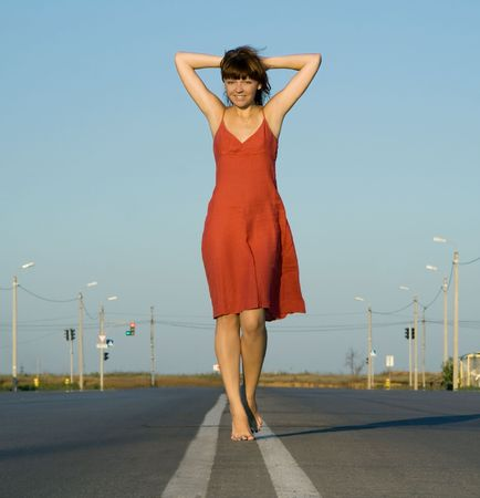 girl in red dress walk barefoot on empty road photo