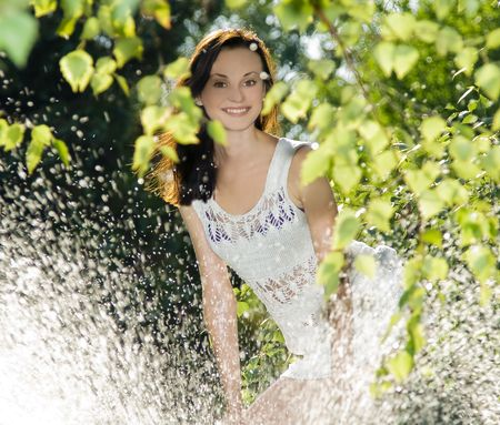 cute brunette in white dress standing behind water splash  photo