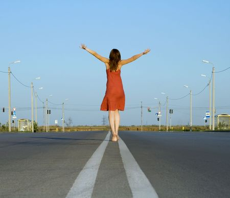 girl in red dress walk barefoot on empty road Imagens - 7494115