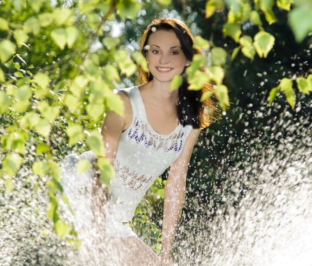 cute brunette in white dress standing behind water splash  photo