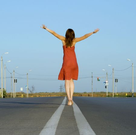 empty road: girl in red dress walk barefoot on empty road