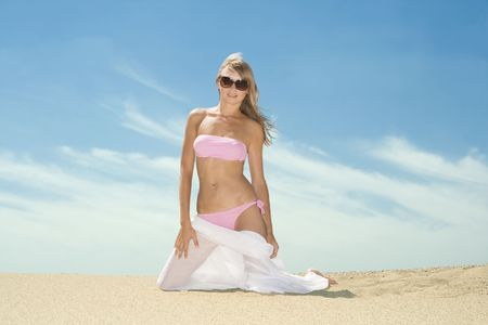 Woman posing on the beach with white silk scarf blowing by wind photo