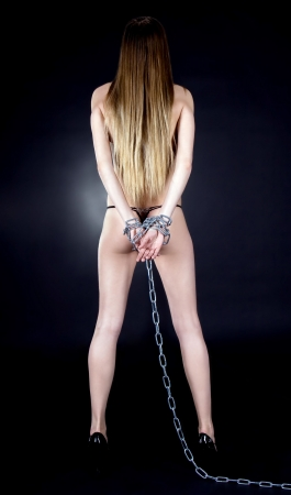 Sexy brunette with nude back in chains over black background