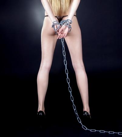 ceppi: Brunette sexy con schiena nuda in catene su sfondo nero  Archivio Fotografico