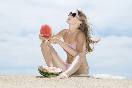 Woman posing on the beach and eating watermelon  photo