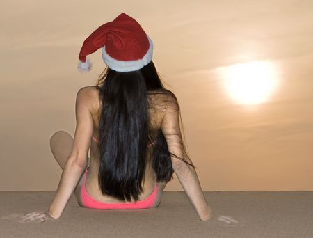 Back view of the girl in Santa's hat looking at sunset photo