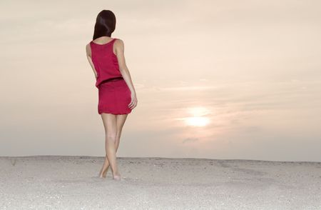 Cute female in red dress walking at the desert in sunset photo