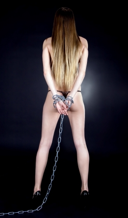 Sexy brunette with nude back in chains over black background photo