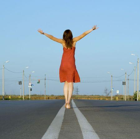 walk in: girl in red dress walk barefoot on empty road
