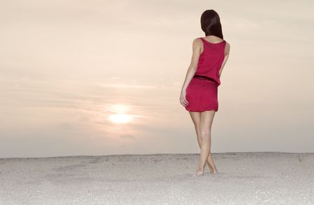 Cute female in red dress walking at the desert in sunset