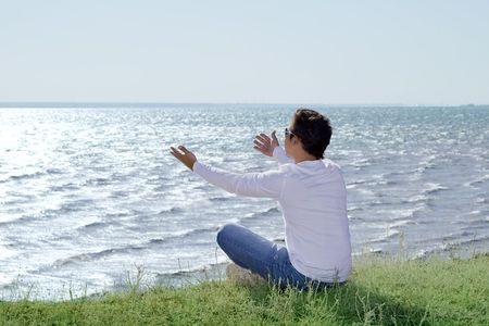 young man  sitting at precipice and looking on the sea shore photo