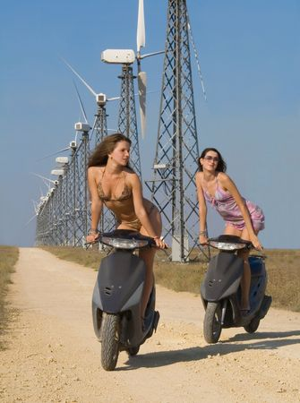 moped: Two girls driving bicycles on the road in wind farm.
