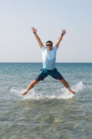 Happy young male jumping from the water photo