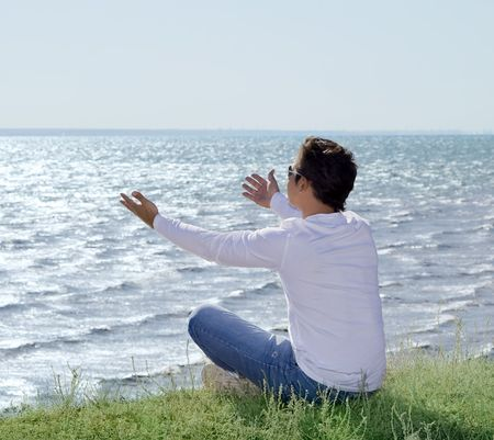 young man  sitting at precipice and looking on the sea shore Stock Photo - 7917520