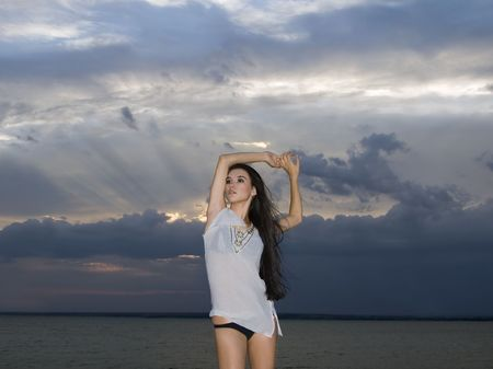 sexy brunette woman over dusk sky at sunset photo