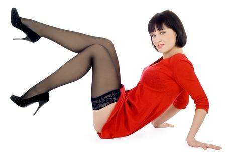 medias mujer: Encantadora dama joven vestido rojo sentado fondo aislado blanco