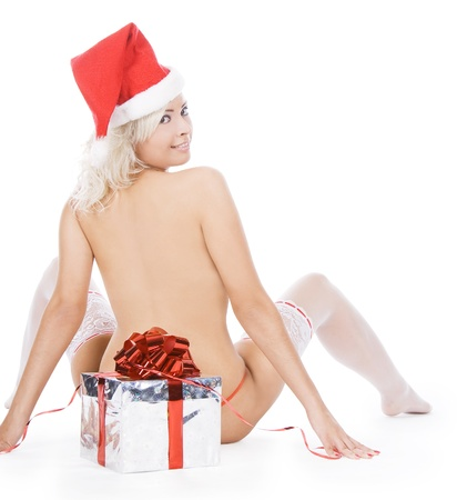 Wonderful female in santa hat and white stockings near Christmas gift