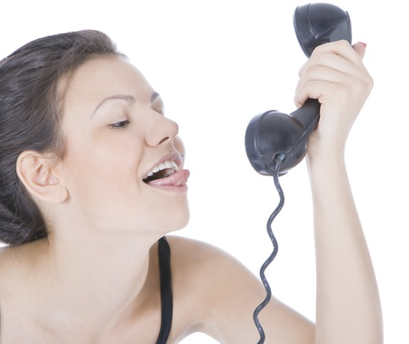 Bright picture of fun brunette showing tongue to phone photo