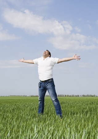 young man moves in a green field of grass to meet the sun Stock Photo - 8647640