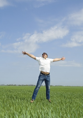 young man jumping a green field of grass   photo